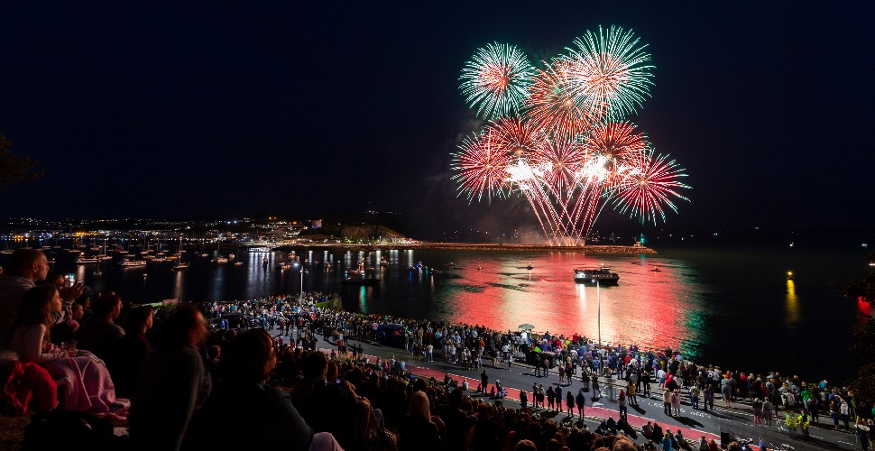Red and green fireworks over Plymouth Sound with a crowd of people watching