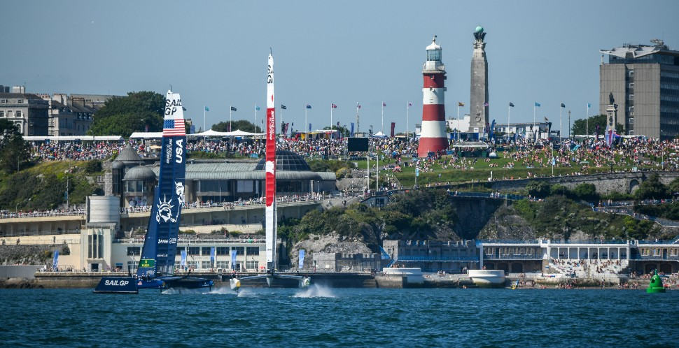 SailGP F50 catamarans racing in front of crowds of people on Plymouth Hoe during the Great Britain Sail Grand Prix