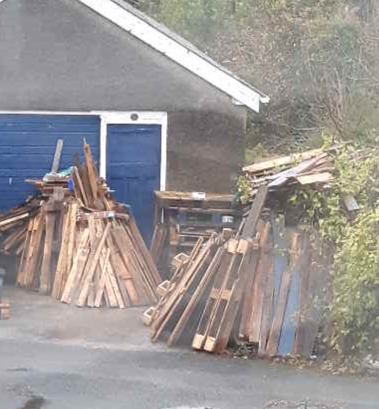 piles of pallets next to a garage