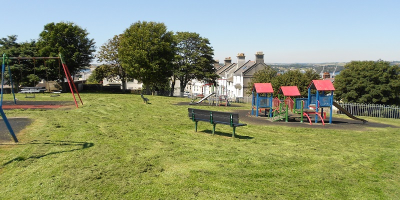 Photograph of a park showing a field covered in grass with a park bench in the foreground and two trees and some houses in the back ground