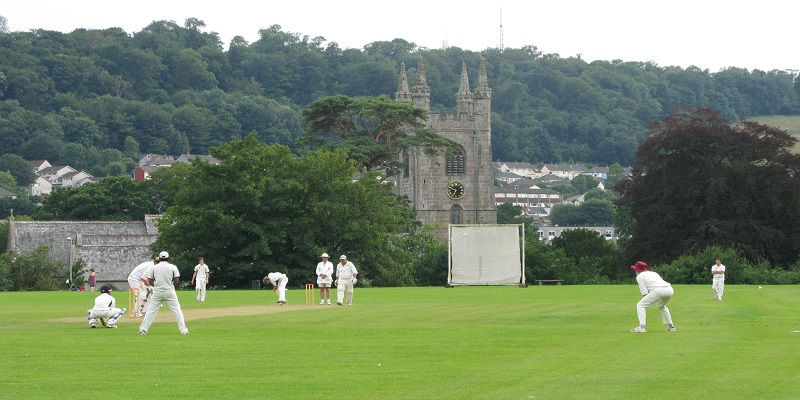 long distance view of people playing cricket in the foreground with church in background